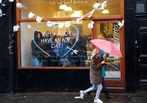 A girl walks past a sandwich shop decorated with a message for the couple