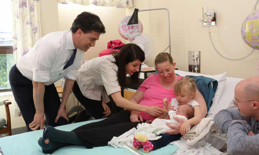 Ed Miliband and shadow health minister, Liz Kendall, talk to new parents Rebecca and Richard Booth with the Booths' newborn baby Mila and her sister Lola.