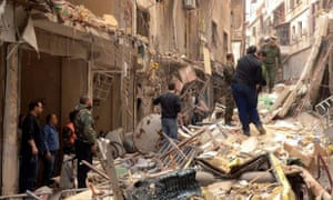 Syrians walk through the rubble following reported rocket attacks by rebel fighters in northern Aleppo.