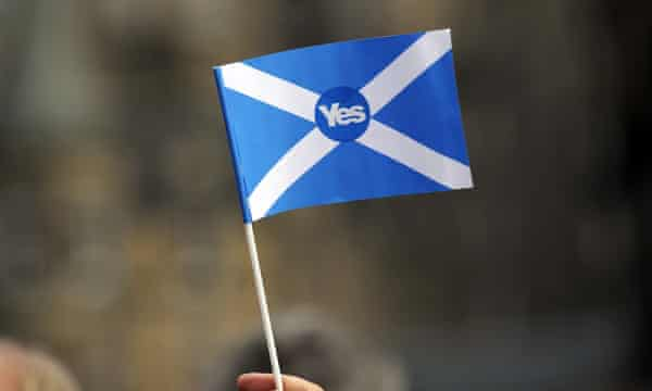 A pro-independence supporter holds a 'Yes' flag