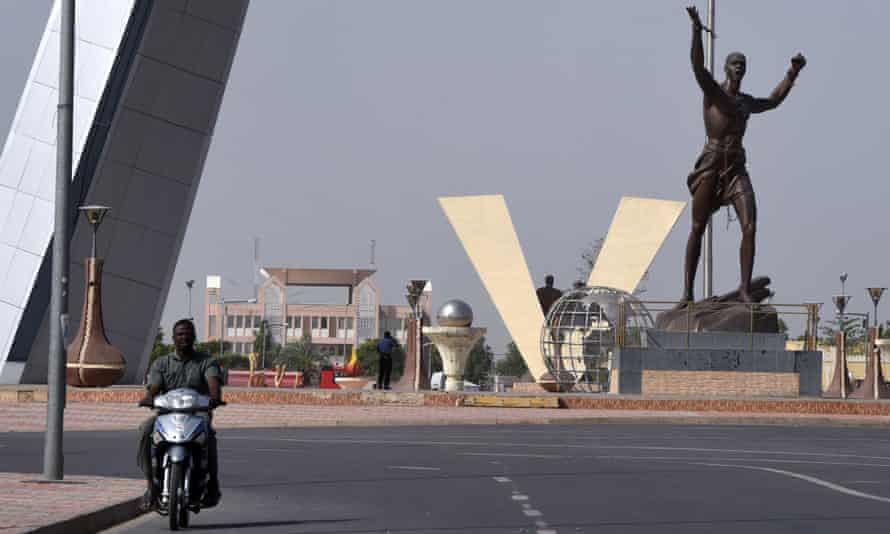 A man on a motorbike rides past La Place de la Nation (Nation Square) in N'Djamena.