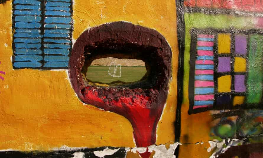 A hole in a wall reveals a football pitch inside the UN-controlled buffer zone dividing Nicosia
