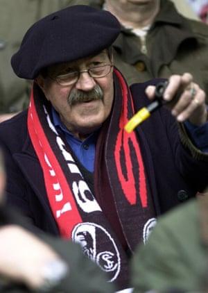 Grass wears an SC Freiburg club scarf as he watches the Bundesliga match between Freiburg and Borussia Dortmund at the Dreisam-stadium in Freiburg, February, 2000.