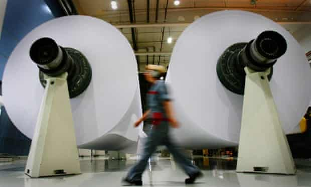 An employee walks past two paper reels at a mill in Oulu, Finland.