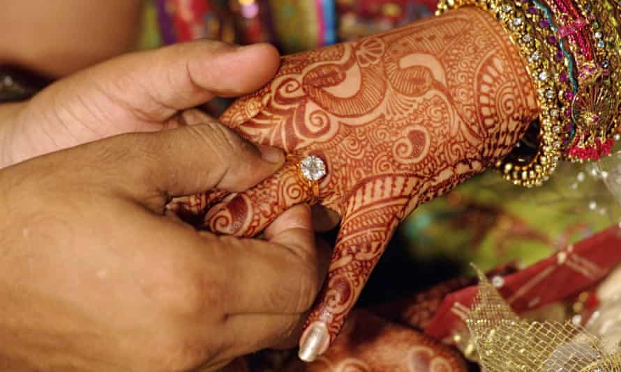 A bridegroom giving a wedding ring to a bride with hands decorated with henna and bangles, India