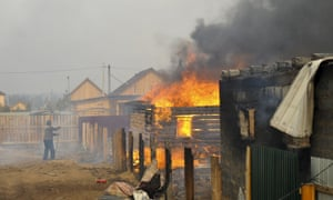 A man tries to save his home from blaze at neighbouring property in Smolenka, Siberia.