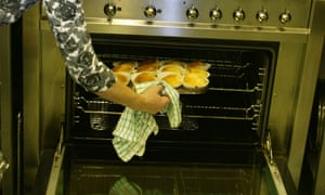 Taking buns out of an oven