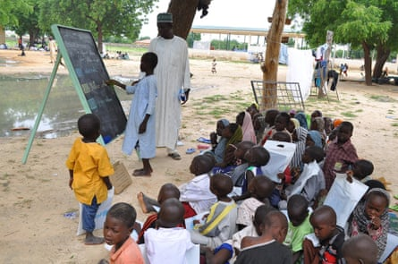 Children who fled their homes following an attacked by Islamist militants in Bama, take a lesson at a camp in Maiduguri, Nigeria