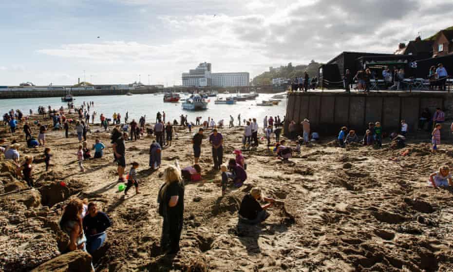 People digging on Folkestone Harbour beach