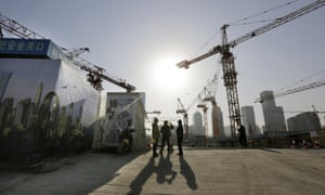 Workers chat outside a construction site in Beijing's central business district, China.