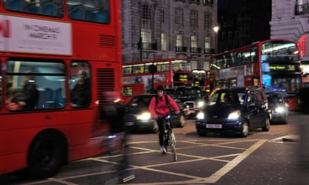 A cyclist negotiating traffic at night in London