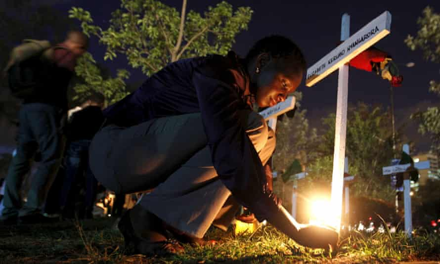 A woman lights a candle in Nairobi at a memorial to remember the Garissa University students killed by al-Shabaab.