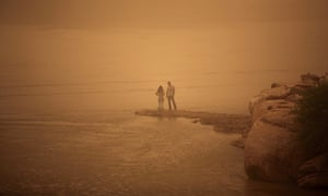 An Iranian couple stands on the shore of the Arvandrud river as a heavy sand storm hits the city of Ahvaz in the southwestern province of Khuzestan.