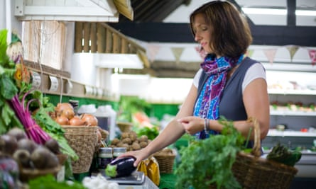 woman picking vegtables from stall