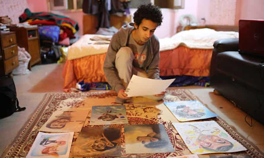 Art student Hussein Adel sitting on the floor his art work spread out