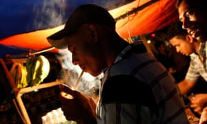 A man lights a cigarette in front of a roadside tea stall in Dhaka, Bangladesh.