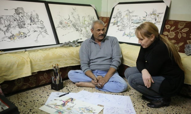 Akeel Korsheed, surrounded by his drawings, with filmmaker  Furat al-Jamil