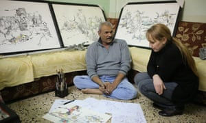 Akeel Korsheed, surrounded by his drawings, with filmmaker  Furat al-Jamil