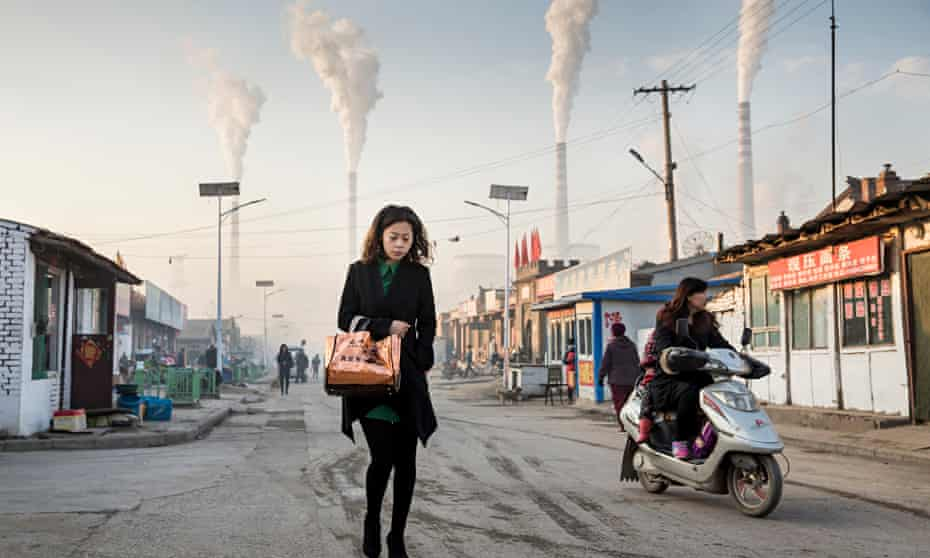 Woman walks through smoke stacks in Shanxi Province, China
