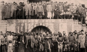 Armenians at the Marash army barracks awaiting execution. (Bottom row)  Above them, the Ottoman governor, Haydar Pasha, and soldiers. April 1915.