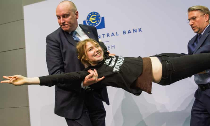 Josephine Witt, a protester who jumped on top of ECB president Mario Draghi's desk during a news conference at the European Central Bank is detained by security.
