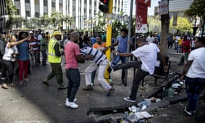 A taxi driver is pushed around during a wave of attacks on foreign nationals in Johannesburg on Wednesday.