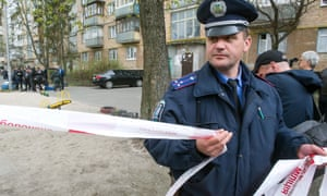 A police officer cordons off the area as police experts examine the body of prominent pro-Russian journalist Oles Buzyna.