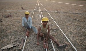 Men work on power transmission lines in Tezpur, India