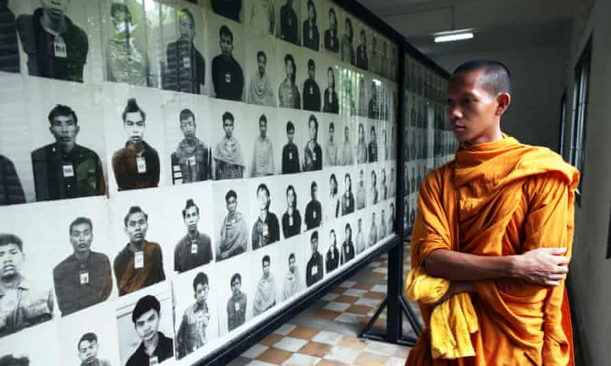 A Cambodian looks at photographs of victims.