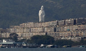 Tsz Shan monastery's bronze-forged white statue, stands behind luxurious houses at Taipo district in Hong Kong.