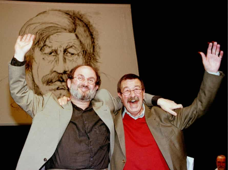 Günter Grass, right, and Salman Rushdie wave to the crowd in front of a portrait of Grass, during his 70th birthday party in Hamburg's Thalia theatre, October 1997.