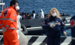 An italian tugboat carrying immigrants arrives at Messina in Sicily on Wednesday.