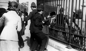 A policeman restrains a demonstrator as suffragettes gathered outside Buckingham Palace in 1914.