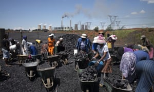 A file photo taken on February 5, 2015 shows women from the coal dust covered and power line pollution exposed Masakhane settlement filling their wheel barrows for a load of free coal provided by a nearby mine in Emalahleni. The Masakhane settlement, mainly consisting of migrant workers who converged to the coal rich Witbank region to search for job opportunities, has no access to the electricity grid, despite being only two kilometres away from the Duvha power station belonging to the embattled South African sole energy provider Eskom, and despite being criss-crossed by high tension power lines.