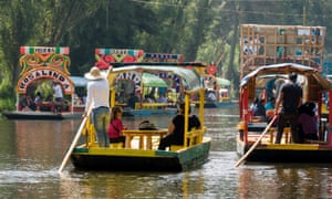 Tourists ride on a bright flat-bottomed boat on Lake Xochimilco