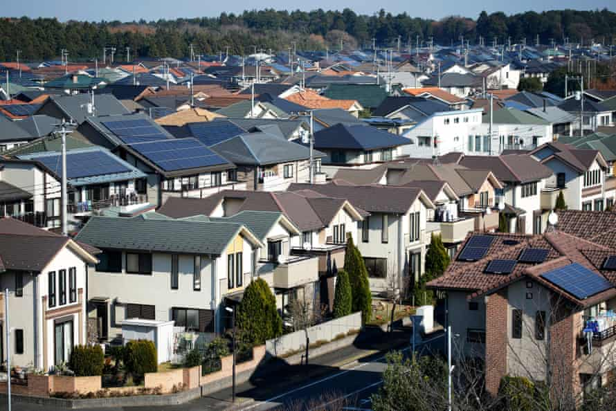 Solar panels sit on house roofs in Inzai, Chiba Prefecture, Japan, on December 9, 2014. Japans recession was deeper than initially estimated as company investment unexpectedly shrank, a blow to Prime Minister Shinzo Abe as he campaigns for re-election on his economic credentials.