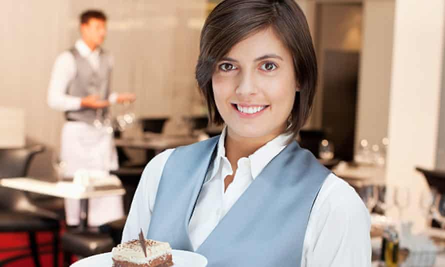 Portrait of smiling waitress holding desserts in restaurant. Image shot 2012. Exact date unknown.