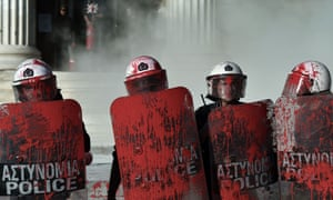 Riot police stand splattered with red paint thrown by protesters outside Athens University.