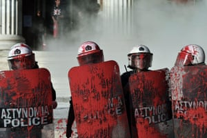 Riot police are splattered with red paint thrown by demonstrators outside Athens University. The protesters demanded the release of families of political prisoners and changes to the anti-terrorist law. The tension arose at the end of a demonstration opposing a gold mine project in the Halkidiki peninsula