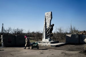 An elderly woman pulls a cart next to a second world war monument in the village of Nikishino, Ukraine. Controversial laws designed to leave the country's Soviet past behind have stoked tension in the war-divided country and prompted an angry reaction from Russia, which called the ban on communist-era symbols 'totalitarian'