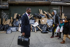 People walk past a pile of protest signs along Flatbush Avenue in Brooklyn, New York, as protesters demonstrate for higher wages. US fast-food workers enlisted students, healthcare workers and racial justice activists to swell the ranks of rallies in 230 cities