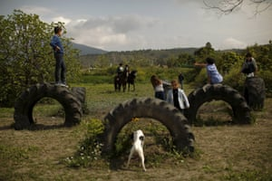 In a photograph by Jon Nazca, a regular contributor to the 20 photographs, children play on tractor tyres in a field while Andalusian jockeys ride their thoroughbred horses after taking part in a classical dressage contest in Coin, Spain