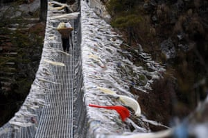 A Nepali porter walks on a suspension bridge over a deep valley near Labja Dorhan on his way to the Himalayan town of Namche Bazar. Mountaineers are making their way to Everest a year after an avalanche killed 16 guides and triggered an unprecedented shutdown of the world's highest peak. Some are returning after being forced to abandon their attempt on the summit in 2014 during the chaos and recriminations that followed the deadliest disaster ever to hit Everest