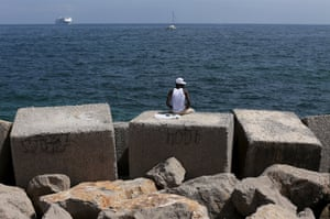 Palermo, Italy A migrant sits on a concrete block in the harbour