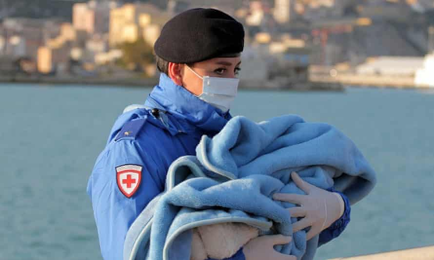 A Red Cross officer carries a baby wrapped in a blanket after rescued migrants disembarked at the Sicilian port of Empedocle.