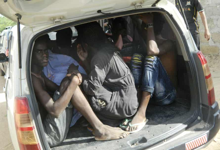 Students of the Garissa University College take shelter in a vehicle after fleeing the attack.