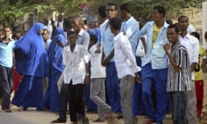 Students gather and watch from a distance outside the Garissa University College.