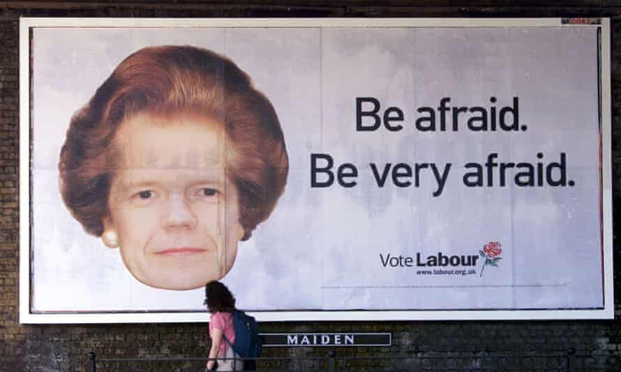 A passing woman looks up at a Labour Party election poster showing Conservative leader William Hague with a the haircut of former prime minister Margaret Thatcher