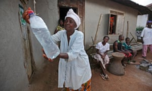 A Liberian woman washes her hands from a bottle of chlorine water to curb the spread of Ebola in Jene Wonde village, November 2014.