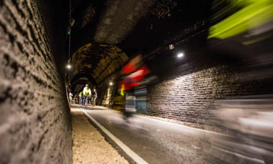 Cyclists riding through the restored Devonshire Tunnel which is part of the Two Tunnels Greenway.
